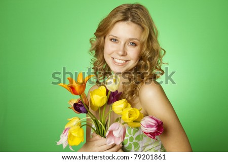 Happy close-up on a green background happy young woman hugging a bouquet of colorful tulips