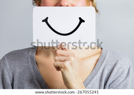 Happy Closeup of a Woman Holding a Smiling Mood Board - stock photo