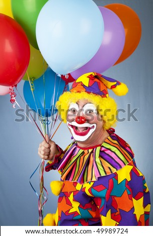 Happy clown with balloons in front of a blue background.