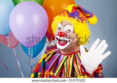 Happy clown with helium balloons, waving hello. - stock photo