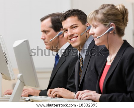 Happy co-workers in headsets working at computers in call center - stock photo