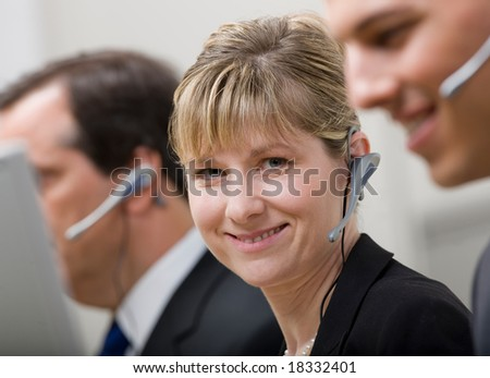 Happy co-workers in headsets working in call center - stock photo