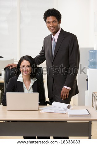 Happy co-workers with laptop at desk