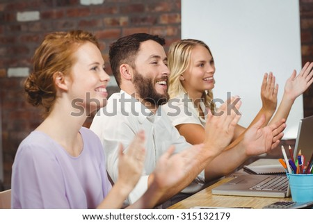 Happy colleagues clapping at meeting in creative office