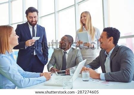Happy colleagues listening to elegant employee at meeting - stock photo