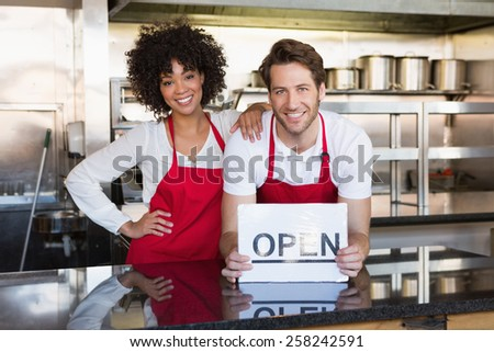 Happy colleagues posing with open sign at the bakery - stock photo