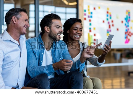 Happy colleagues using mobile phone in the office - stock photo