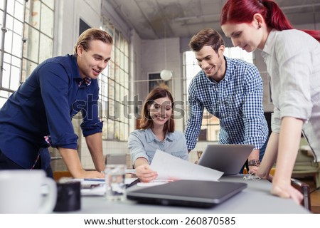 Happy College Friends Discussing What is in the Document at the Table Inside the Office. - stock photo