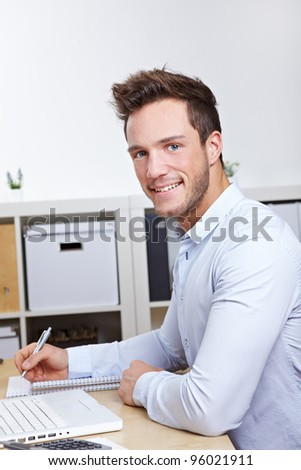 Happy college student learning at desk with laptop computer - stock photo