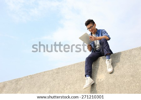 Happy College student man using digital tablet pc and sit, asian male - stock photo