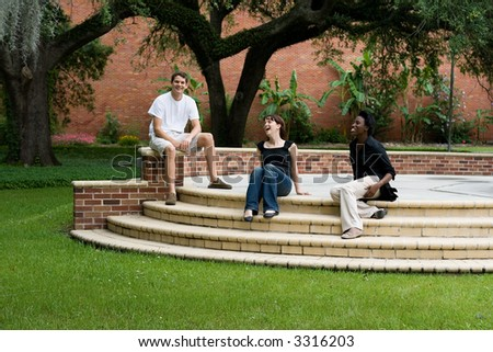 happy college students hanging out on campus - stock photo
