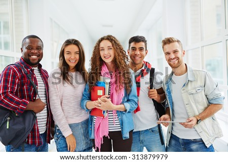Happy college students looking at camera with smiles - stock photo