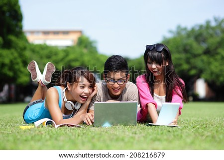 Happy College students using laptop and tablet pc on campus lawn, asian - stock photo