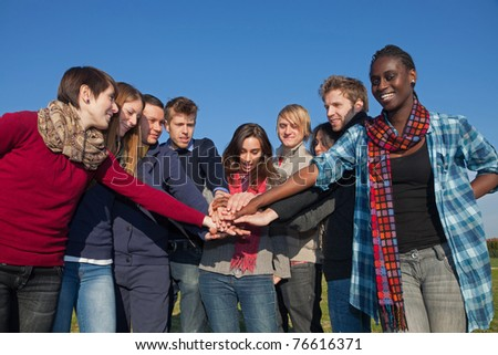 Happy College Students with Hands on Stack - stock photo