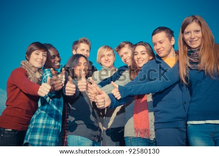 Happy College Students with Thumbs Up - stock photo