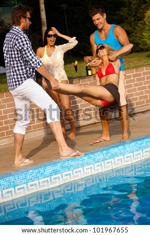 Happy companionship having fun at summertime by swimming pool. - stock photo