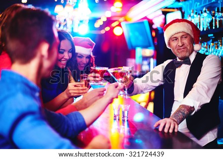 Happy company cheering up by counter with barman in Santa cap near by - stock photo