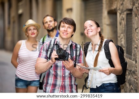 Happy company of impressed travelers during city walking - stock photo