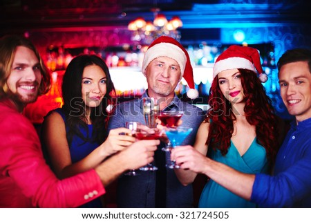 Happy company with drinks cheering up during party in bar