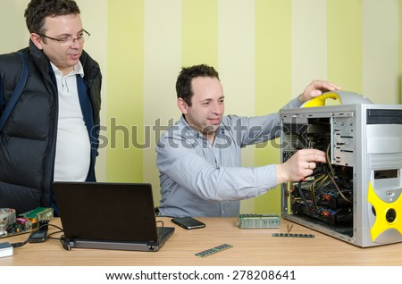 Happy computer engineer repairing broken computer while conversing with male customer at the office. Isolated on retro striped green and yellow wallpaper. - stock photo