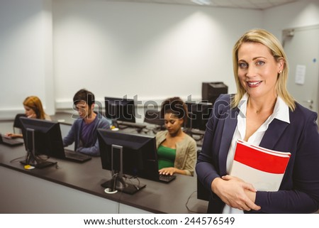 Happy computer teacher smiling at camera during her class at the university - stock photo