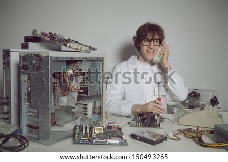 Happy computer technician in his laboratory is talking on the phone - stock photo