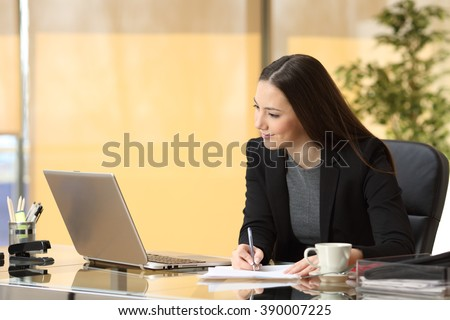 Happy concentrated businesswoman working online and taking notes sitting in a desktop at office - stock photo