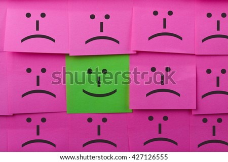 Happy concept. Background of sticky notes. Green sticky note is among pink sticky notes. - stock photo