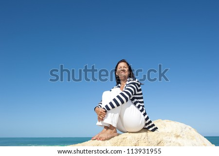 Happy confident and attractive senior woman  relaxed active retirement holiday at sea, isolated with ocean and blue sky as background and copy space.
