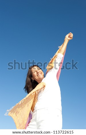 Happy, confident and attractive senior woman with positive attitude, isolated with blue sky as background and copy space. - stock photo