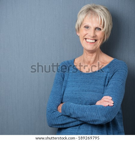 Happy confident attractive senior woman with blue eyes and a wide beaming smile standing with folded arms against a blue background with copyspace - stock photo