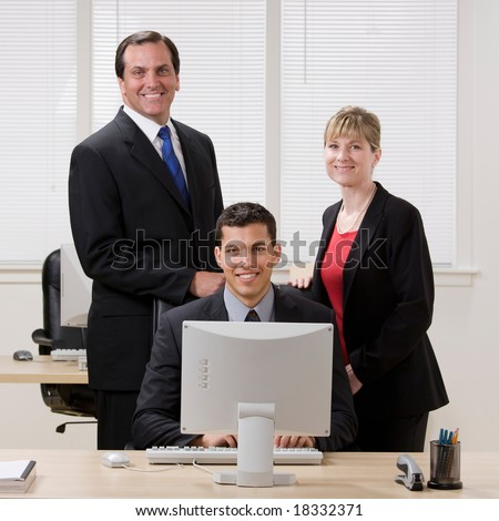 Happy, confident co-workers standing at desk - stock photo