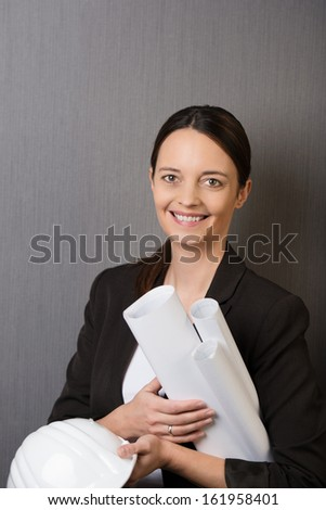 Happy confident female architect or structural engineer holding a hard hat and a stack of rolled blueprints under her arm against a grey background - stock photo