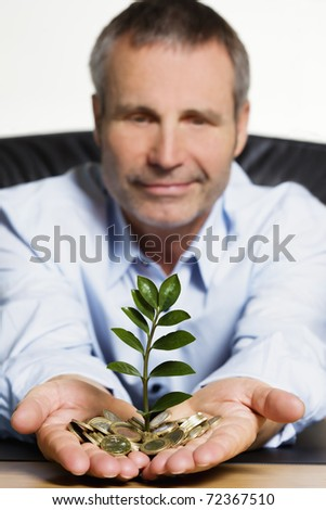 Happy confident senior businessman sitting at desk  presenting a green plant growing out of a pile of Euro coins symbolizing growth of financial wealth. - stock photo