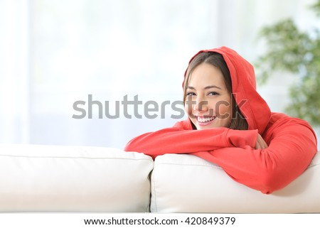 Happy confident teen girl in red posing and looking at camera at home - stock photo