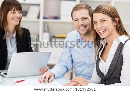 Happy confident young couple in a meeting sitting discussing a presentation and paperwork with their female adviser - stock photo