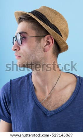 happy confident young man in hat and sunglasses standing over blue background
