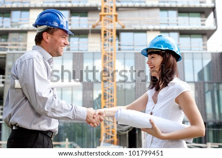 Happy construction specialists sealing the deal at a construction site - stock photo