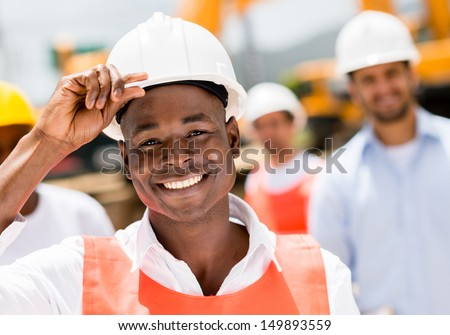 Happy construction worker at a building site wearing a helmet - stock photo