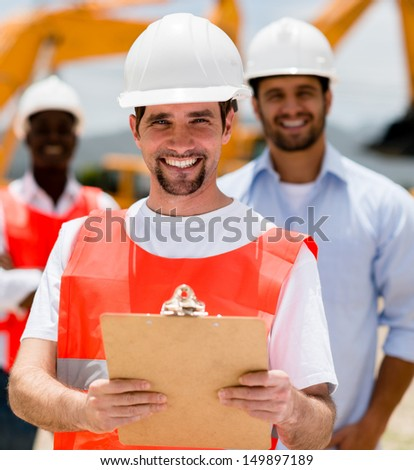 Happy construction worker holding a clipboard and smiling  - stock photo