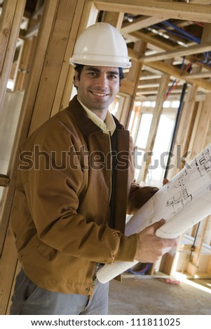 Happy construction worker holding blueprints - stock photo