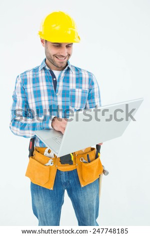 Happy construction worker using laptop against white background