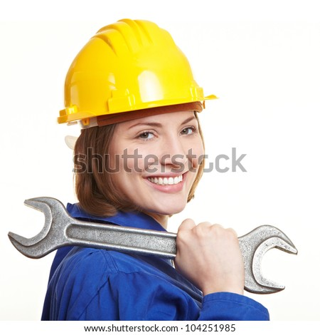 Happy construction worker with helmet carrying big wrench on shoulder - stock photo