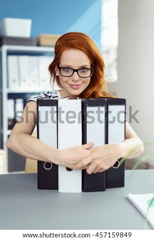 Happy contented young redhead businesswoman wearing eyeglasses sitting at a table in the office clutching binders and smiling - stock photo