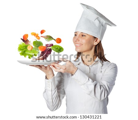 Happy cook woman holding a dish with floating vegetables / Chef serving empty plate with vegetables in suspension isolated on white
