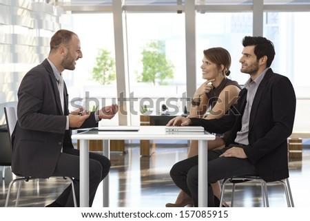 Happy corporate business people talking at meeting at office. - stock photo