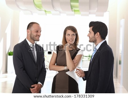 Happy corporate business people talking in office corridor. - stock photo
