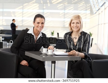 Happy corporate businesswomen meeting at coffee table in office. - stock photo