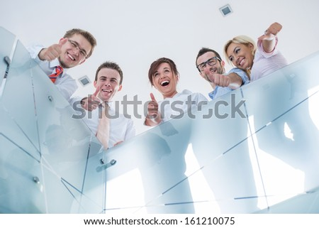 Happy corporate people posing showing thumbs up in a modern office - stock photo