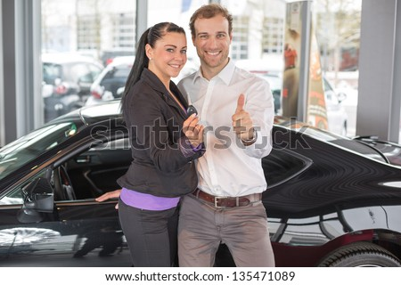 Happy couple after buying an automobile in a car dealership - stock photo